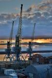 在河的起重机在日落的口岸的 库存照片