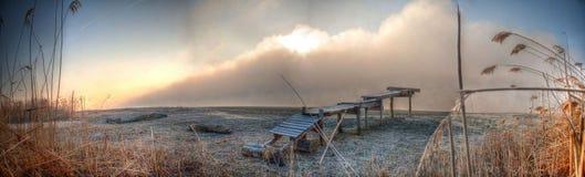在河美好的黎明的日落在有一朵大云彩和渔桥梁的一条有薄雾的河 免版税库存照片