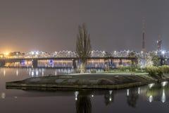 在河道加瓦河在晚上,拉脱维亚的有启发性里加铁路桥 免版税库存照片