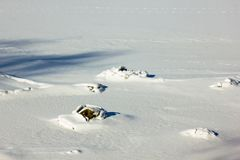 在河部分结冰的小岩石在一个晴朗的冬日 库存图片