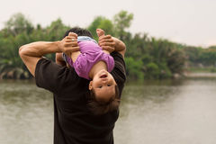 在河附近生演奏和运载他的他的肩膀的孩子 免版税库存照片