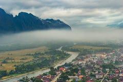在河附近的与薄雾的村庄和山 免版税库存图片