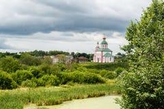 在河附近的俄罗斯正教会云彩背景的  库存照片