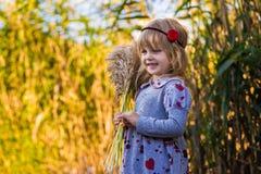 在河附近的快乐的小女孩有芦苇的 免版税图库摄影