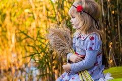 在河附近的快乐的小女孩有芦苇的 库存照片