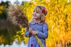 在河附近的快乐的小女孩有芦苇的 图库摄影