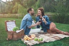 在河附近的快乐的男人和妇女饮用的酒 免版税库存照片