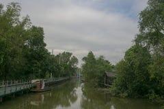 在河附近骑自行车方式、小船和树 库存照片