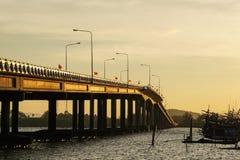 在河,海的桥梁早晨太阳上升,小船,大象旗子泰国 图库摄影