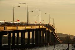 在河,海的桥梁早晨太阳上升,小船,大象旗子泰国 库存图片