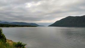 在河/湖的多云天-沿岸航行,浇灌表面岸 免版税库存图片
