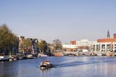 在河Amstel的看法在阿姆斯特丹,荷兰的首都,有小船、蓝天、树和大厦的 免版税库存图片