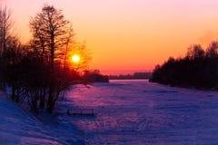 在河kototoraya pokryda冰和雪的银行的华美的日落 库存照片