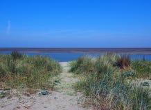 在河wyre的银行的草覆盖的沙丘在弗利特伍德lancashire附近的与镇静大海和被日光照射了天空 库存照片