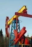 在油井的一pumpjack在冬天树木繁茂的风景 免版税库存图片