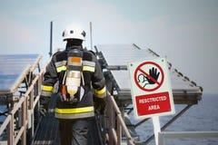 在油和煤气产业的消防队员,成功的消防队员在工作,战斗机的火衣服与火和衣服为保护火 库存图片