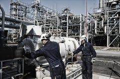 在油和煤气产业里面的精炼厂工作者 库存图片