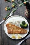 在油油煎的面包渣的鱼用米和硬花甘蓝 免版税库存图片