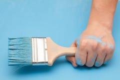 在油漆报道的男性手,拿着木背景表面上的一支画笔,被绘用蓝色油漆 免版税库存图片