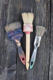 在油漆的三支画笔在木背景 免版税库存图片