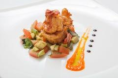 在油煎的菜的油煎的虾在一块白色板材 免版税库存照片