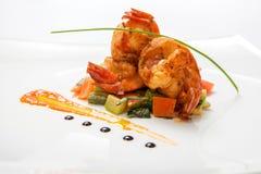在油煎的菜的油煎的虾在一块白色板材 库存照片