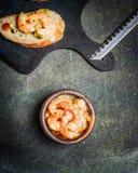 在油调味汁的虾Scampi在黑暗的土气背景的土气碗 库存照片