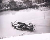 在沼泽的被弄翻的汽车困住的人 库存照片