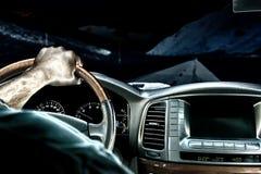 在沿在山中的夜路移动汽车的方向盘的一个人的手 图库摄影