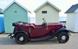 在沿海岸区散步停放的经典红色汽车在海滩小屋前面停放了 库存图片