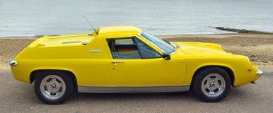 在沿海岸区散步停放的经典黄色莲花欧罗巴汽车 免版税图库摄影