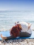 在沿海的妇女执行的joga 免版税库存照片