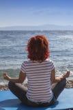在沿海的妇女执行的joga 库存照片