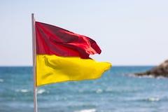 在沿海的红色黄旗生命概念安全 库存照片