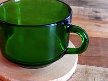 在沿海航船木头表上的减速火箭的绿色咖啡杯 免版税图库摄影