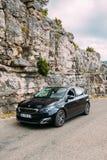 在法国山自然背景的黑颜色标致汽车308汽车  免版税库存照片