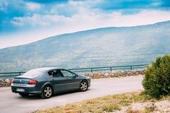 在法国山自然风景背景的标致汽车407汽车  库存照片