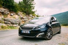 在法国山na背景的黑颜色标致汽车308汽车  图库摄影