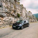 在法国山na背景的黑颜色标致汽车308汽车  免版税库存图片