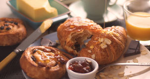 在法国早餐的倾吐的蜂蜜用酥皮点心和橙汁 库存图片
