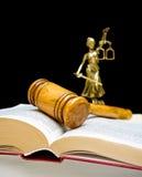 在法律书籍的惊堂木在黑背景。垂直的照片。 免版税库存图片