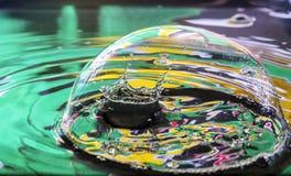 在泡影内的水飞溅 免版税图库摄影