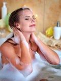 在泡末浴的妇女洗涤的头发 免版税库存图片