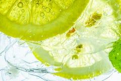 在泡沫腾涌的苏打水,汁液的柠檬糖 免版税库存照片