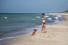 在波儿地克的海滩的妇女和儿童休息 图库摄影