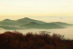 在波希米亚的一座美丽的山的秋天日出。从雾增加的小山峰顶。 免版税库存照片