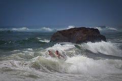 在波浪的孩子在巨石城附近在海洋 免版税库存照片