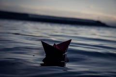 在波浪的红色纸小船 免版税图库摄影