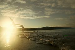 在波浪的Sunbed在日落 免版税图库摄影