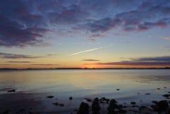 在波罗的海的日出有在前景的岩石的 图库摄影